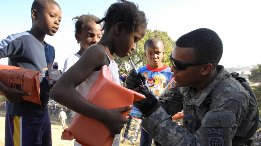 Spc. Juan Valencia marks the fingernail of a small girl to indicate she has gone through the distribution line in Port-au-Prince, Jan. 18, 2010