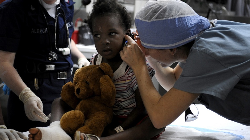 U.S. Navy members assigned to the U.S.N.S. Comfort treats a patient in Port au Prince, Haiti, Jan. 21, 2010.