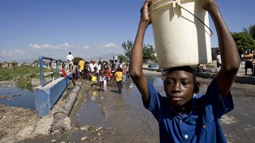 A boy in Cité Soleil carries away a hard-won bucket of water from a broken water pipe where many Haitians struggled for their share. The shanty town of Cité Soleil has been left with severely diminished water resources after a powerful earthquake rocked the area on 12 January.