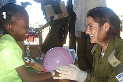An aid worker speaks with a young Haitian girl at a field hosptial.
