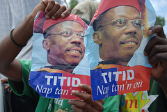 "Supporters of ex-president of Haiti Jean Bertrand Aristide hold signs bearing his nickname ""Titid"" that read ""We are waiting for you,"" in Kreyol."
