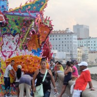 """People walk down the Malecón, in front of """"Occidente con esteroides"""" (West with steroids) by Stainless."""