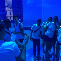 """Students pose from within """"Proyecto-Reality - Cubo Azul"""" (Reality Project- Blue Cube) by Rachel Valdés, which features a mirror that reflects out onto the ocean."""