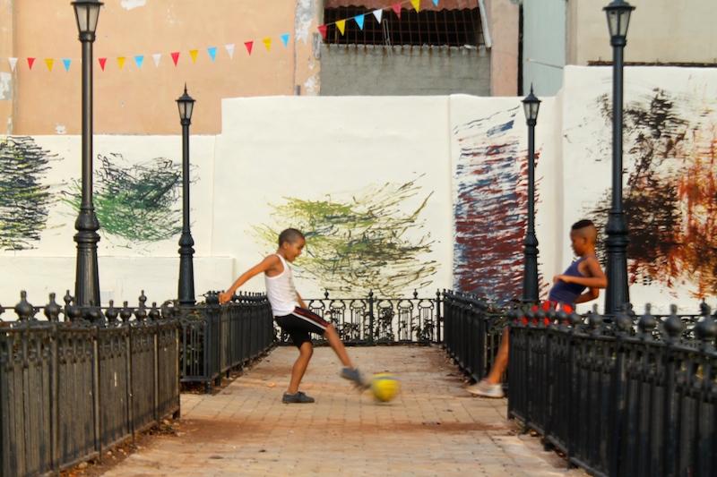 """Kids play soccer within """"Delirios"""" (Deliriums) by Ernesto García Sánchez."""
