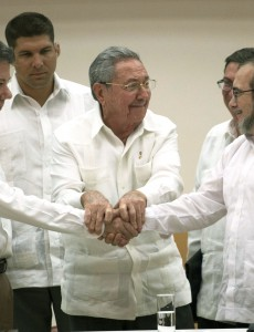 Colombian President Juan Manuel Santos shakes hands with FARC commander Timochenko after their announcement Wednesday of an imminent peace deal. (Image: César Carrión, public domain)