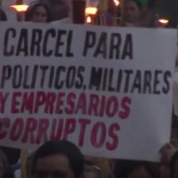 """Prison for corrupt police, soldiers and business people,"" reads a sign during a protest in Honduras in June. (Image: YouTube)"