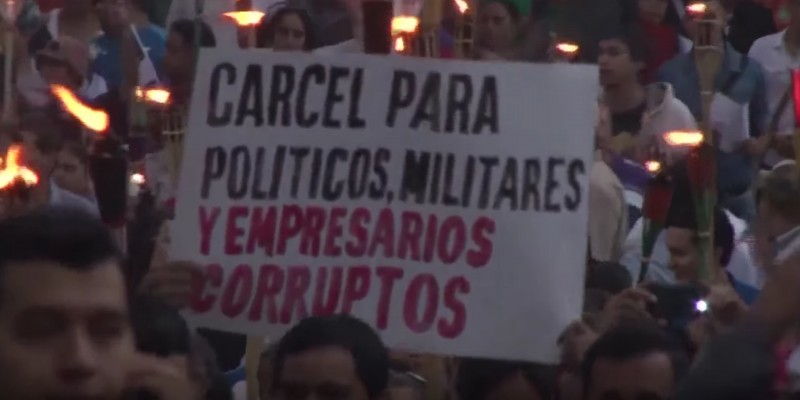 """""""Prison for corrupt police, soldiers and business people,"""" reads a sign during a protest in Honduras in June. (Image: YouTube)"""