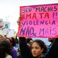 "A Brazilian protester in Rio de Janeiro's Copacabana Beach, holding a sign that reads, ""Your Sexism Kills!! No More Violence"""