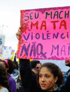 "A Brazilian protester in Rio de Janeiro's Copacabana Beach, holding a sign that reads, ""Your Sexism Kills!! No More Violence"""