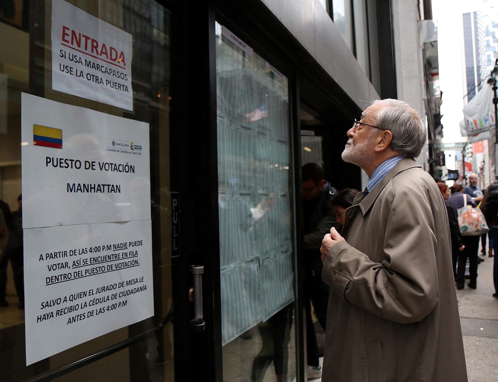 A Colombian man looks at a list of assigned voting tables at the Colombian Consulate in Manhattan on referendum day. (Image: Monica Espitia)